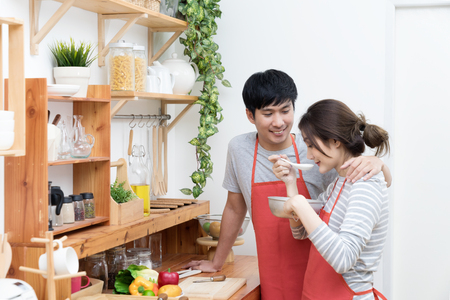 Happy asian young couple make cooking in kitchen, Man looking and smilling to woman, Wife preparing and testing food for dinner with husband.