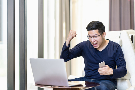 Young happy excited asian man watching laptop and celebration, winning, satisfaction, cheerful action with success work.