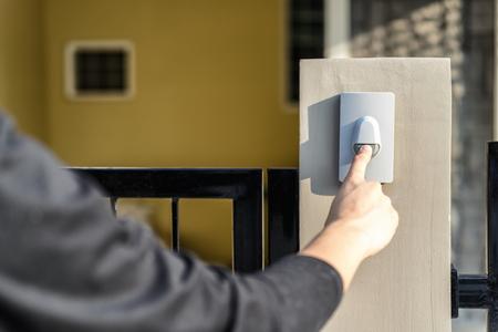 La mano del hombre presionando un botón de timbre con luz solar. Ciérrese encima de visitante de la mano y del dedo que suena el timbre del timbre Los huéspedes presionan la campana detrás de la puerta de entrada a casa.