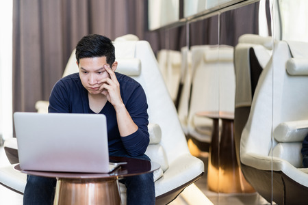 Stressed out asian man freelancer looking computer laptop and holding hand on his face. Young asian student tried, failure, stess, strain, exhausted and thinking his work.