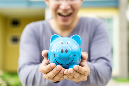 Happy asian man holding blue piggybank with front outdoor home background. Smiling rich property owner loan, mortgage or installment for house. Investment in real estate business and debt concept Stock Photo