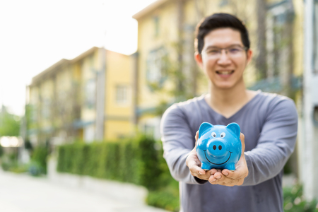 Happy asian man holding piggybank with front outdoor home background copy space on left. Smiling rich property owner loan, mortgage or installment for house. Investment in real estate business and debt concept Foto de archivo
