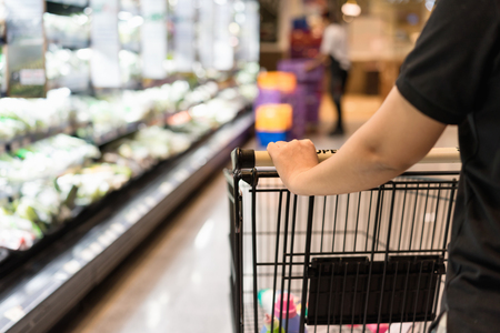 Close up shopper wifehouse woman's hand is pushing a shopping cart at supermarket, retail, supermart, store or groceries aisle. Have copy space on left hand side. Stock Photo