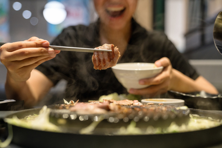 Woman's hand use chopsticks hold korean pork grilled, pork slice roasted, BBQ or Yakiniku.Happy smile hungry asian girl have meal lunch or dinner at restaurant.Funny and Enjoy eating lifestyle concept
