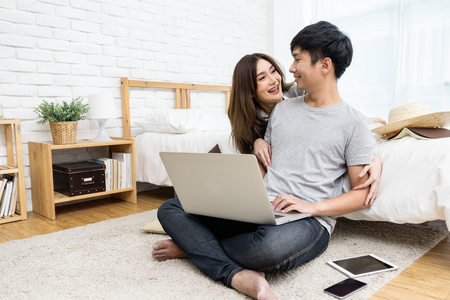 Young asian couple looking together using computer laptop internet shopping online or searching data honeymoon trip travel at bedroom in house.Happy lover hug each other and smiling on bed at  home Banco de Imagens