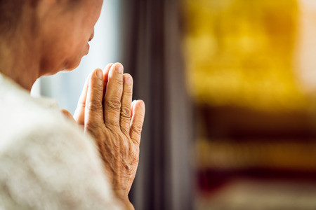 Close up Grandmother's hand pray respect for faith spirituality and religion (Buddha, Christian). Asking God for good luck, success, forgiveness.Power of religion, worship, belief.Warm tone