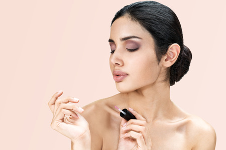 Young asian beautiful woman face portrait natural make-up applying transparent nail or painting nails. Nail care, manicure, spa, beauty concept.