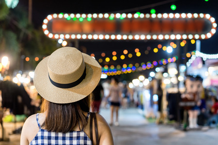 Young asian tourist looking, walking and shoping at street night market in thailand. Back view asia woman tourism travel outdoor night city trip on holiday vacation. Foto de archivo