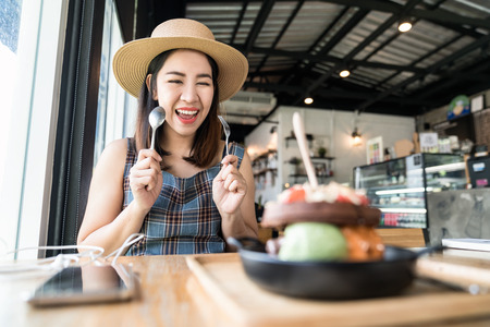 Young asian woman eating icecream, cake, or waffle; food at cafe restaurant.