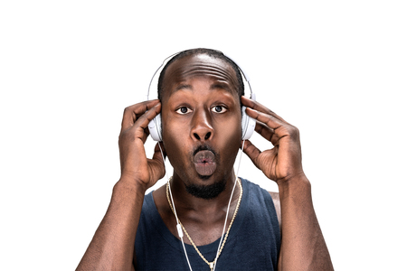 Portrait black man listening music with white background. African or amarican man listen and wow or omg action face. Happy, shock and surprise emotion.