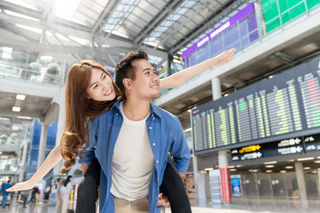 Young asian couple having fun and playing at airport terminal. Happy asia lovers are traveling honeymoon trip by airplane. Asia tourism, or holiday vacation travel concept.