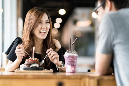 Asian couple enjoying date and talking in cafe. Happy smile woman chatting and laughing with boyfriend at restaurant cafe. Stock Photo