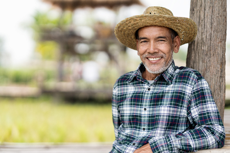 Portrait happy mature man is smiling. Senior farmer with white beard feeling confident. Elderly asian man sitting in a shirt and looking at camera.