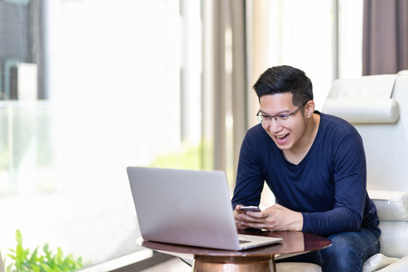 Happy excited asian man celebrate with smartphone and computer laptop, success or happy action. Freelancer or Entrepreneur using technology and start up modern office with copy space