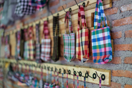 Handmade's small bag, gift hanging on the wooden wall for sale in souvenir store with plaid pattern design or loincloth texture. Thai rural craft material concept with copy space.