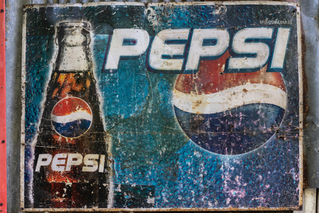 Ratchaburi, Thailand - May 21st, 2018: A vintage advertising sign board for the Pepsi Cola brand. Pepsi logo printed on board and hanged at antique store. Non-alcoholic soft drink sold worldwide.