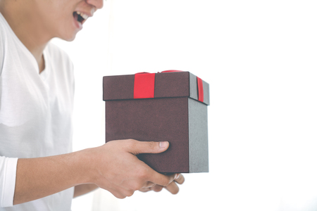 Cropped image of asian romantic guy with white shirt hold a present with red ribbon on his hands with white background and copy space. Surprise on anniversary,newyear,valentine or christmas concept.