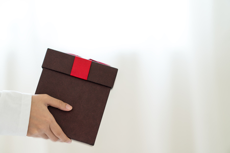 Womans hand holding present red box. Woman give gift with copy space. Box for christmas, new year, valentine day or anniversary on side view Banco de Imagens