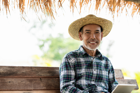 Asian adult modern agriculture technology concept of smart farmer using digital tablet at home farm or crop field monitor report smile and sitting on wood rustic bench wear hatshirt with copy space.