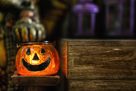 Halloween pumpkin lantern in antique store with smiley face and orange candle light glowing show besides wooden desk table. Candle illuminated decoration concept with dim light and copy space.