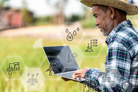 Asian adult modern agriculture technology concept of smart farmer smile using/hold laptop to monitor/manage report on green rice field background with copy space.Internet of thing and digital farming.