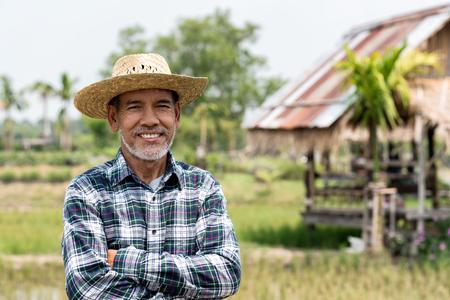 Retrato de hombre maduro feliz está sonriendo. Granjero senior con barba blanca sintiéndose confiado. Anciano asiático de pie, acarició su brazo y con una camisa y mirando a la cámara. Foto de archivo