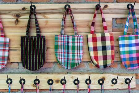 Handmade's small bag, gift hanging on the wooden wall for sale in souvenir store with plaid pattern design or loincloth texture. Thai rural craft material concept with copy space front view. Stock Photo