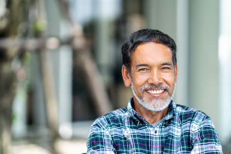 Portrait of happy mature man with white, grey stylish short beard looking at camera outdoor. Casual lifestyle of retired hispanic people or adult asian man smile with confident at coffee shop cafe. Stock Photo