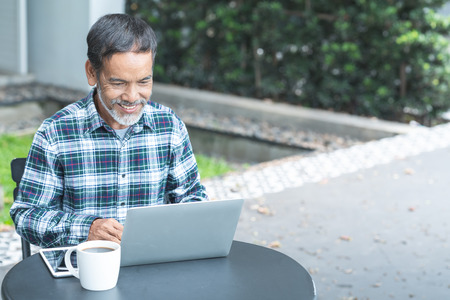 Smiling attractive mature man with white, grey stylish short beard using smartphone gadget serving internet in modern office,co-working space or coffee shop. Old man using social network technology. Stock Photo