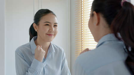Young adult female asia people self love cheer up pep talk before job interview deep breathe inhale standing look in front of mirror smile at home in mental health care or work career stress relief.