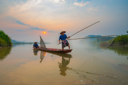 Fishermen in action when fishing in the mekong river , Thailand.