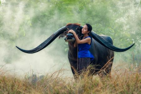 buffalo grass: Thai young woman farmer with buffalo
