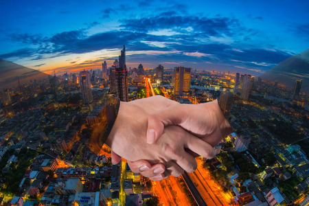 夕暮れの背景に街並みバンコクのビジネス地区の空撮で実業家のハンド シェークの二重露光。