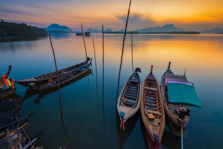 日の出の水の反射によって湖のマリーナでボートします。
