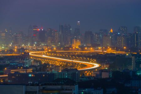 Aerial view of a city skylines and the highway heading into the Bangkok city at night. Stock Photo