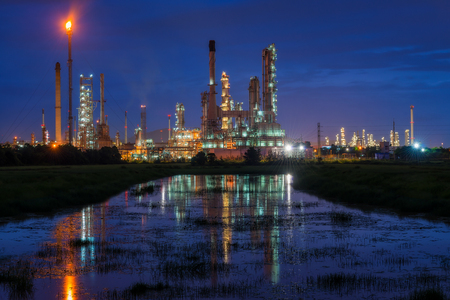 Oil refinery or petroleum refinery industry landscape with reflection at twilight time in the morning. Industrial estate of Thailand, industrial process plant where crude oil is processed and refined. Stock Photo