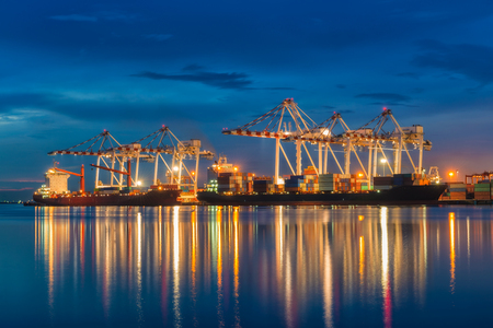 Industrial port with containers cargo ship in the trade port, shipping, transportation, logistic import export at sunset, twilight time.