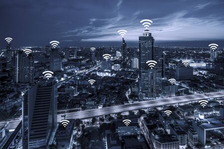 Wifi ネットワーク接続概念ブルートーン夕暮れの背景に街並みバンコクのビジネス地区の空撮。