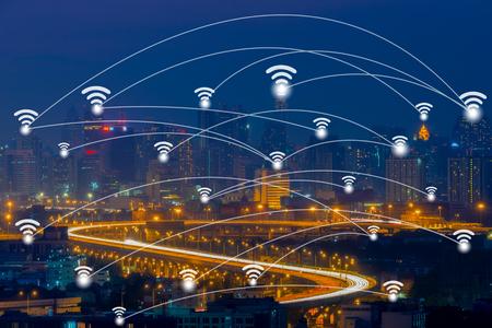 夕暮れの背景に都市景観地区の空撮の Wifi ネットワーク接続概念。