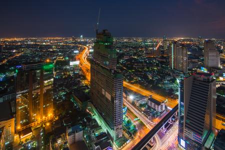 高いビルを建設クレーンと夜のイルミネーション