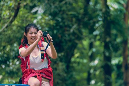 バックパックを取ると美しい若い女性は夏の森林の美しい風景を写真します。 写真素材