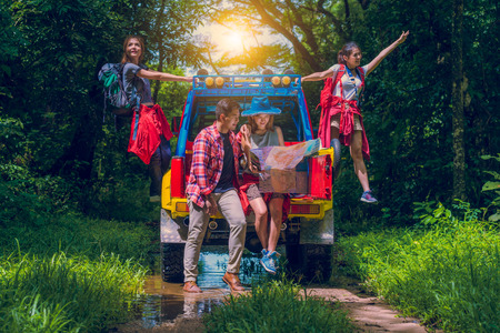 幸せアジア若い旅行者オフロード 4 wd 車とフォレストで、マップと別の方向を探している若いカップル 2 つは 4 wd 車で楽しんでいます。