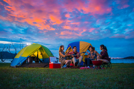 Camping of happy asian young travellers at lake, asian man and women group, relaxing, sing a song and cooking, at sunset. Banque d'images