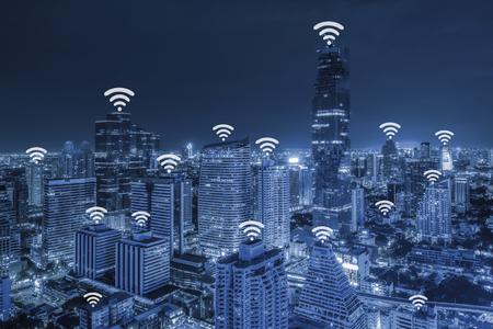 Wifi ネットワーク接続概念ブルートーン夕暮れの背景に都市景観地区の空撮。