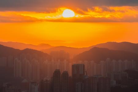香港の街のスカイラインを昇る太陽