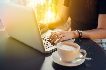 若い女性の机に座って、朝のコンピューターでオンライン作業をノート パソコンで入力します。ネットワー キングおよび職業の概念は、手をクロー