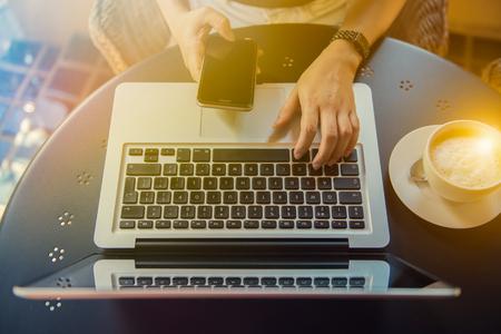 若い女性の机に座って、ノート パソコンと携帯電話で入力手すぐ。屋外カフェで働く女性。