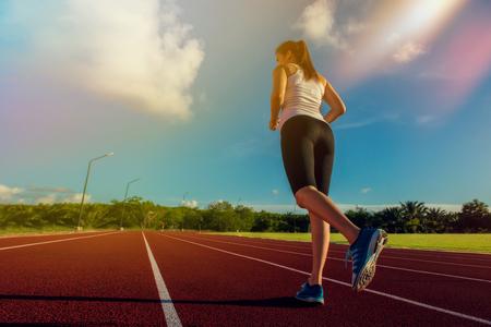 スポーティな女性スポーツ ウエア、靴、足に夕方フォーカスのスタジアム トラック上で実行します。フィットネスやワークアウト ウェルネスのコ