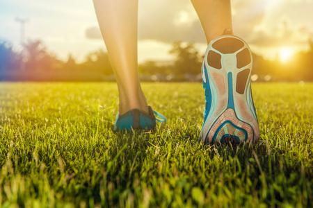 ランナーの足の練習走行靴に草のクローズ アップ。フィットネスやワークアウト ウェルネスのコンセプト。