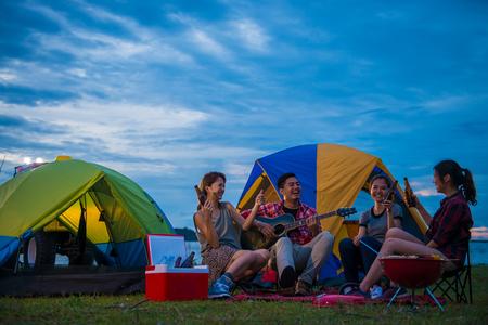 湖、アジア人、女性グループで幸せなアジアの若い旅行者のキャンプ、リラックス、歌を歌う、料理、夕暮れ時。 写真素材